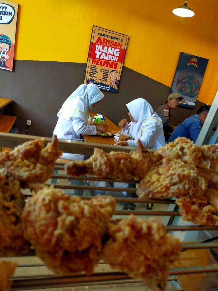 Pelanggan ayam geprek juara sedang menikmati berbagai ayam yang disajikan